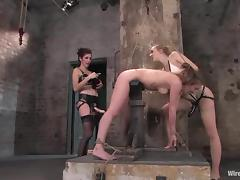 A slut gets tortured by two sexy bitches in a basement tube porn video